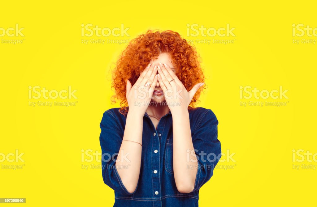 See no evil concept. Closeup portrait young redhead curly hair woman closing covering eyes with hands can't look hiding avoiding situation isolated yellow background. Human emotion face expression stock photo