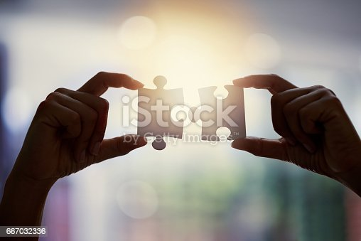 Closeup shot of an unidentifiable businesswoman holding two puzzle pieces together