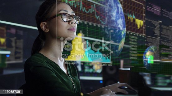 Stock photo of a young Asian woman looking at see through global & environmental data whilst seated in a dark office. The data is projected on a see through (see-thru) display.