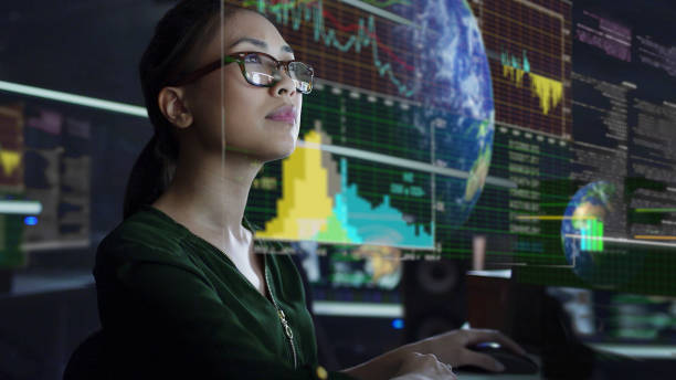See through screen Stock photo of a young Asian woman looking at see through global & environmental data whilst seated in a dark office. The data is projected on a see through (see-thru) display. data stock pictures, royalty-free photos & images