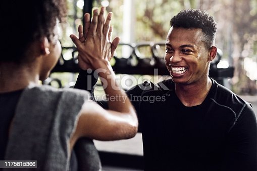 Shot of a young man and woman giving each other a high five at the gym