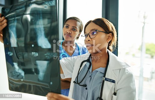 Shot of two medical practitioners analysing x-rays in a hospital