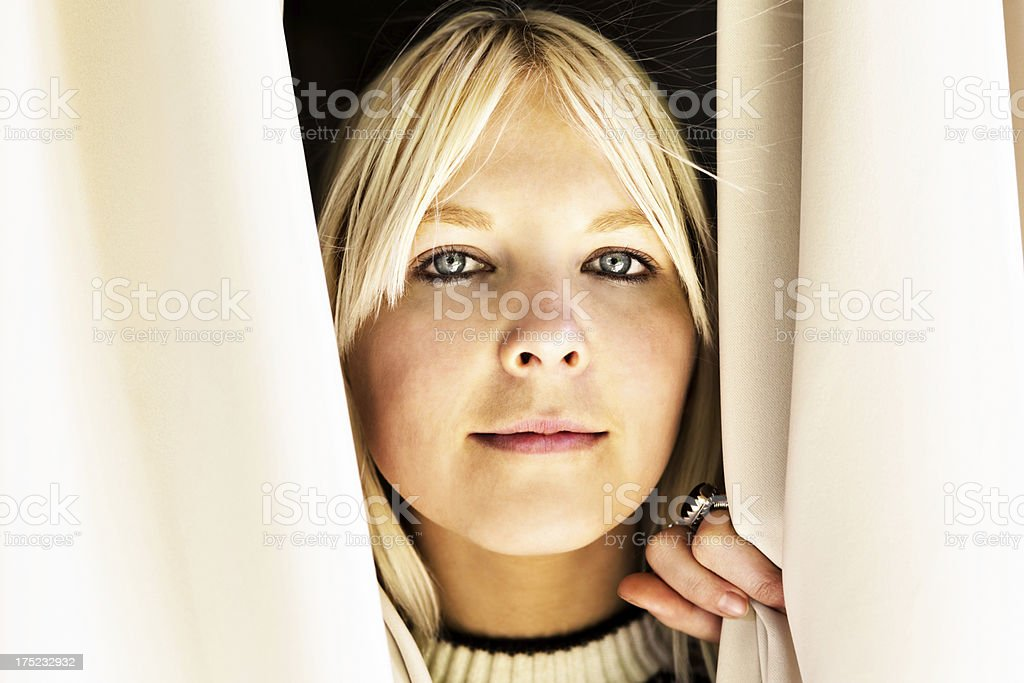 I see you! Cute but serious blonde peeping through curtains royalty-free stock photo