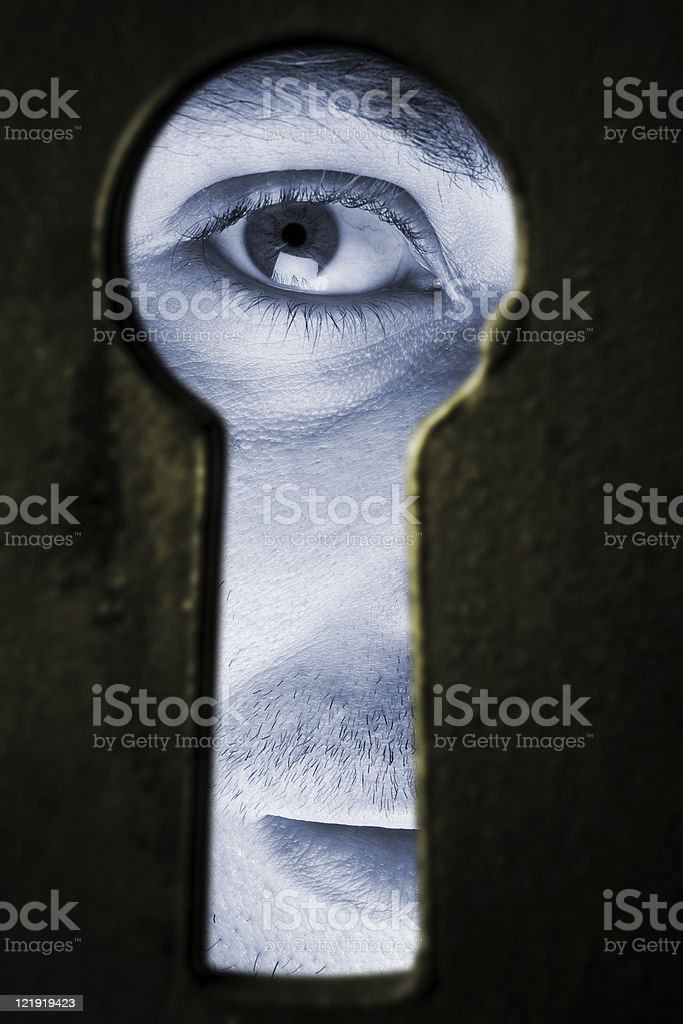 I see you! - man looking through keyhole stock photo