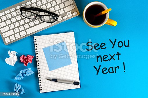 888342518 istock photo See you next year - memo at blue office table. 2018 new year coming 899398836