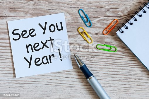 888342518 istock photo See you next year - written on a memo at the office table. 2018 new year coming 899398962