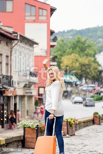 Young woman tourist waving goodbye, Veliko Tarnovo, Bulgaria