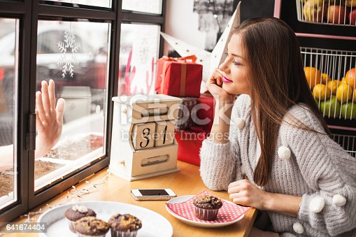 Young couple saying goodbye to each other, girl is sitting in cafe with her hand on her chin and her boyfriend is outside of the coffee shop trying to reach her, touching the display window with his hand