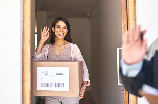 Shot of a young woman waving goodbye to a delivery man