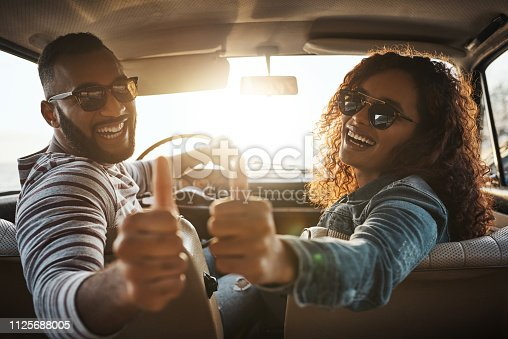 Shot of a young couple giving thumbs up on a road trip