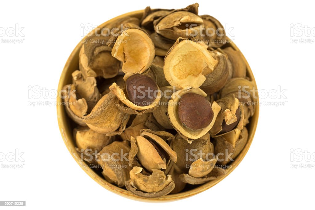 Seed and shell covers of Sacha inchi peanut, capsult fruit nut in a wooden bowl stock photo