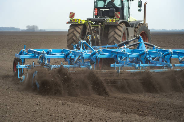 seedbed cultivator working in farm field stock photo