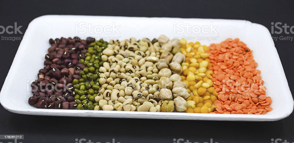 seeds, grains on white plate in black background vertical royalty-free stock photo