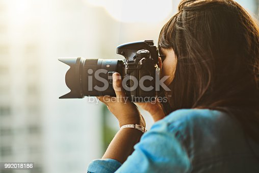 Shot of a woman taking pictures with her camera outside