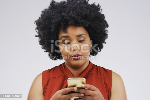 Studio shot of a young woman using a mobile phone against a grey background