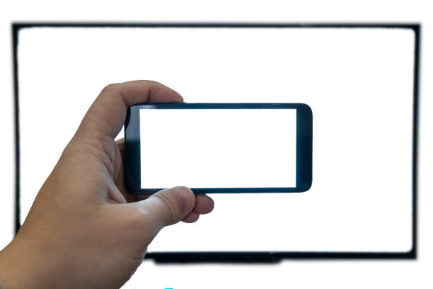 Seeing only through a screen concept. Man holding phone in front of a tv stock photo