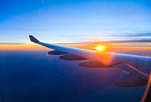 Sunset under aircraft wing skyline view from airplane in flight.