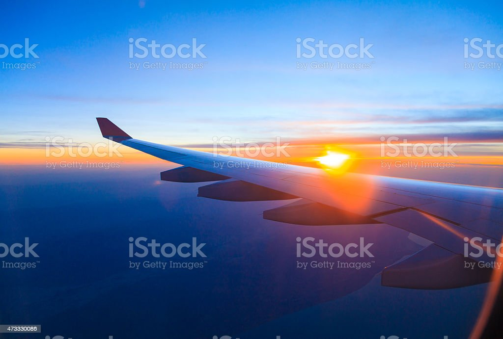 Seeing the sunset on flight stock photo