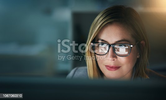 Shot of a young businesswoman working late on a computer in an office