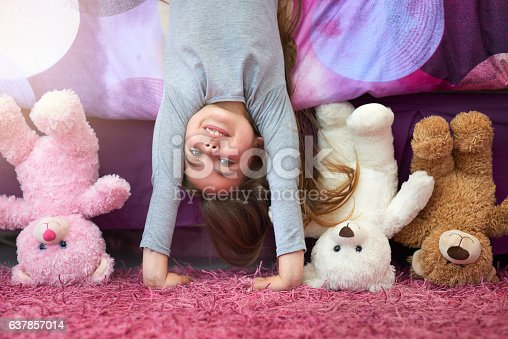 Portrait of a cute little girl doing a handstand in her bedroom at home