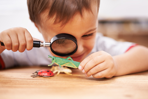 Shot of a young boy inspecting his toys with a magnifying glass