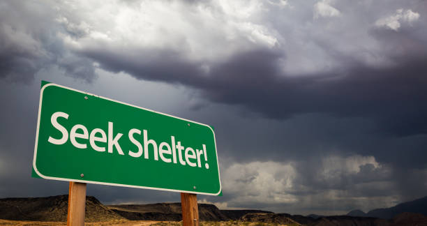 Seek Shelter Green Road Sign and Stormy Clouds Seek Shelter Green Road Sign with Dramatic Clouds and Rain. sheltering stock pictures, royalty-free photos & images