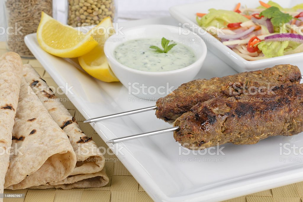 2 seekh kebabs on a white square plate stock photo