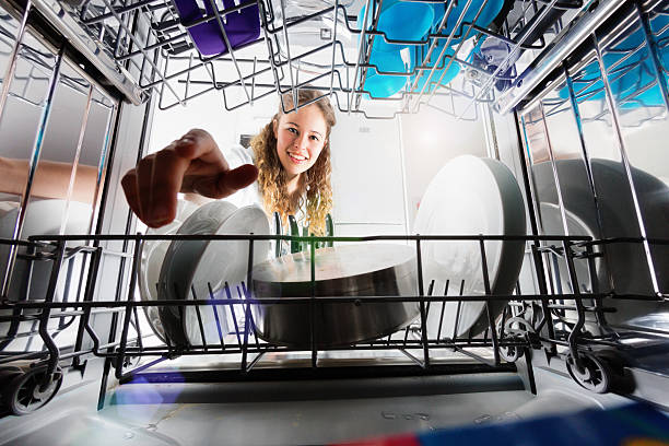 Seen from inside dishwasher, cute smiling girl loading or unloading Seen, unusually, from inside the dishwasher drum, a pretty blonde teenager smiles as she loads ir unloads dishes. dishwasher stock pictures, royalty-free photos & images