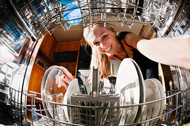 Seen from inside drum, pretty blonde loads the dishwasher Seen, unusually, from inside the dishwasher drum, a pretty blonde smiles as she loads dishes. dishwasher stock pictures, royalty-free photos & images