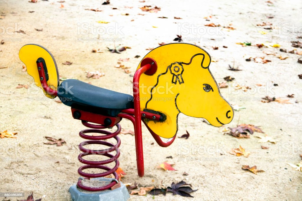 Seesaw, children outdoors playground toy in horse shape. stock photo