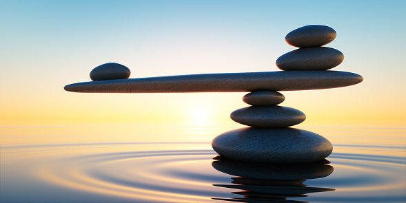 Stack of stones in calm water with seesaw in the evening sun