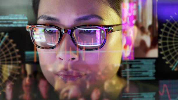 See-thru data screen watcher. Close up stock photo of an Asian woman carefully studying moving data on her computer screen, the screen is unusual as it is transparent and the camera is looking through the back of the screen. scrutiny stock pictures, royalty-free photos & images