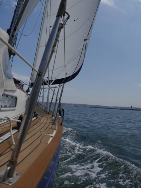 Segelboot nähert sich Land Ein Segelboot unter vollen Segeln nähert sich der Küste cherbourg stock pictures, royalty-free photos & images