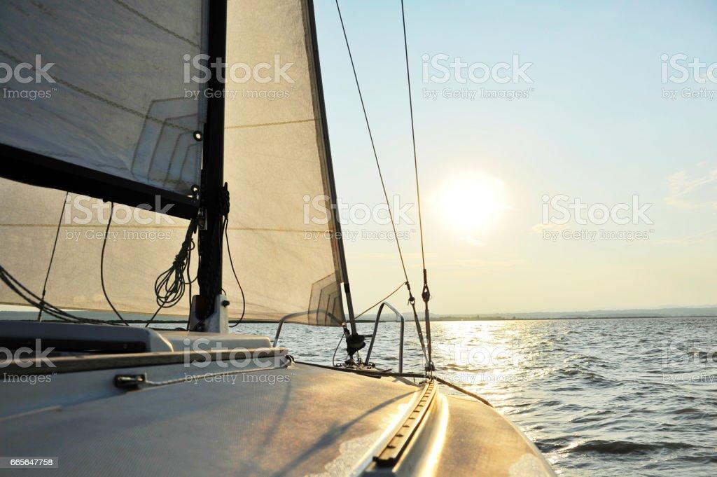 Segelboot segelt in die untergehende Sonne – Foto