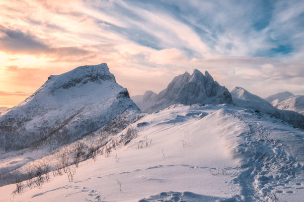 Segla mountain with snowy hill in colorful morning sky at Senja Island stock photo