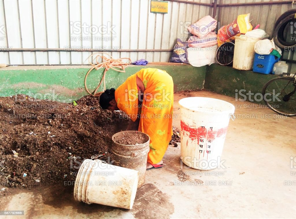 Segregation of wet waste Pune, India - 16th March, 2016: Wet waste segregation for recycling by Swach waste picker in afternoon. Swach is first wholly owned cooperative for waste pickers in India which provides waste management services to citizens of Pune. Adult Stock Photo