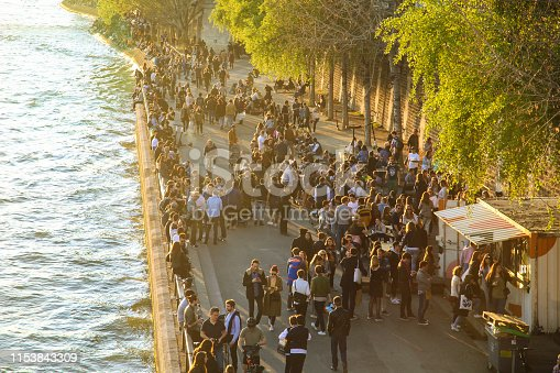 Crowd on the riverbank of Seine in Paris, France.