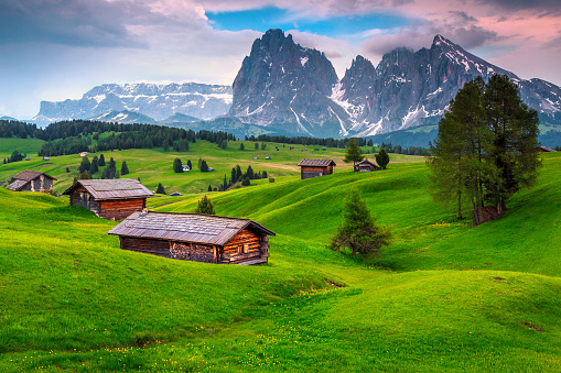 istock Seiser Alm resort and wooden chalets at sunset, Dolomites, Italy 1128634487