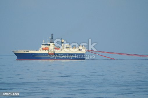 A seismic survey ship pulling survey equipment (streamers). Seismic survey ships map the subsea geology using the seismic sound produced by air guns towed behind the vessel. The information is is used to locate oil and gas deposits.