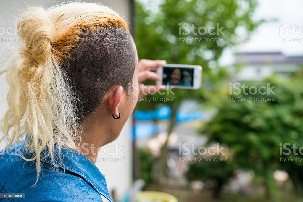 Sejfie of man with Iroquois hair style stock photo