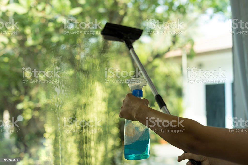 Selected focus Hand spraying window with special cleaner stock photo