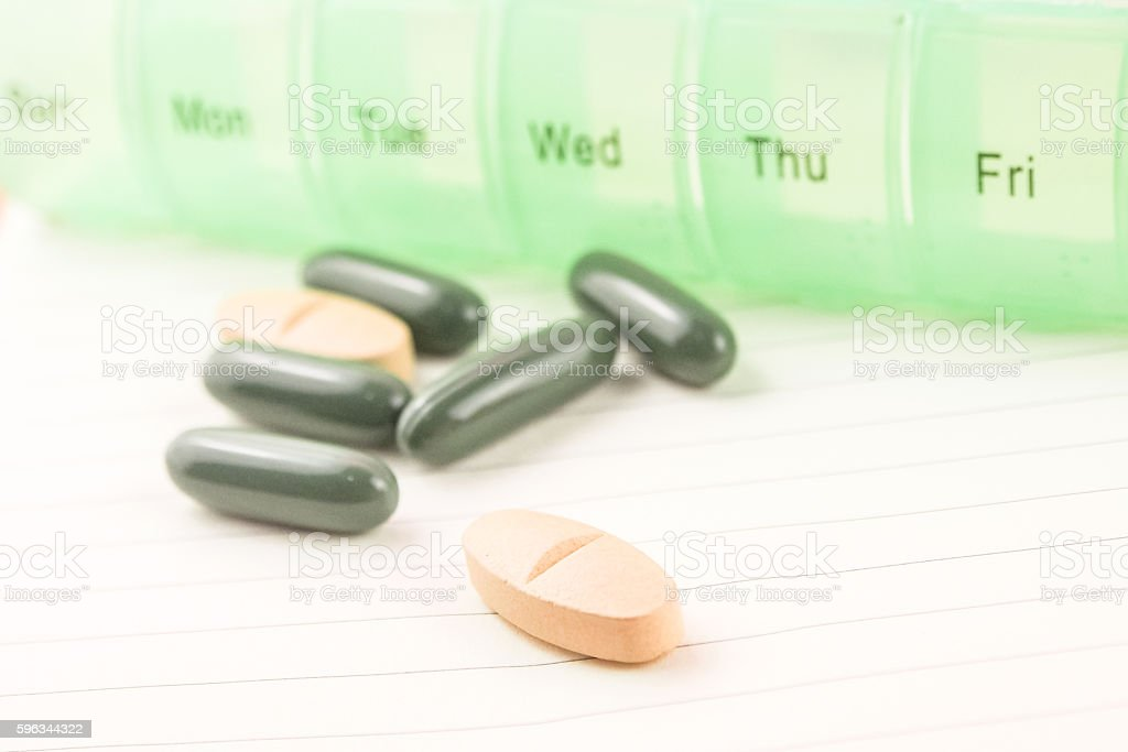 selected focus pill with daily pill box background Lizenzfreies stock-foto