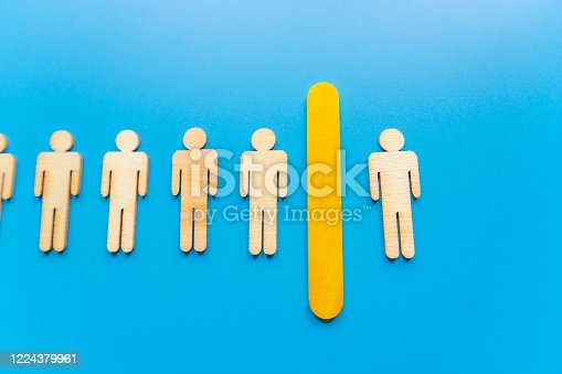 898212112 istock photo Selected wooden figure on blue background. The concept of finding an employee in business. HR manager search employee. Group leader. 1224379961
