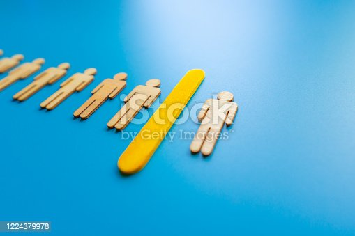 898212112 istock photo Selected wooden figure on blue background. The concept of finding an employee in business. HR manager search employee. Group leader. 1224379978