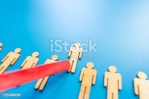 898212112 istock photo Selected wooden figure on blue background. The concept of finding an employee in business. HR manager search employee. Group leader. 1224380250