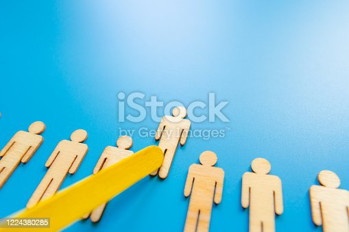 898212112 istock photo Selected wooden figure on blue background. The concept of finding an employee in business. HR manager search employee. Group leader. 1224380285