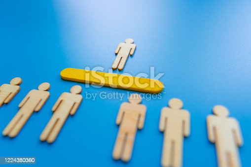898212112 istock photo Selected wooden figure on blue background. The concept of finding an employee in business. HR manager search employee. Group leader. 1224380360