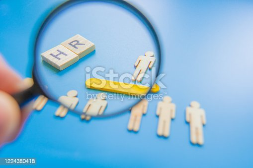 898212112 istock photo Selected wooden figure on blue background. The concept of finding an employee in business. HR manager search employee. Group leader. 1224380418