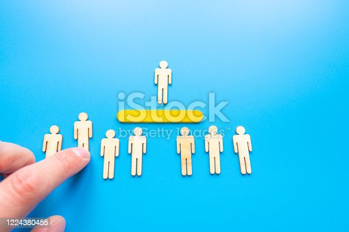 898212112 istock photo Selected wooden figure on blue background. The concept of finding an employee in business. HR manager search employee. Group leader. 1224380455