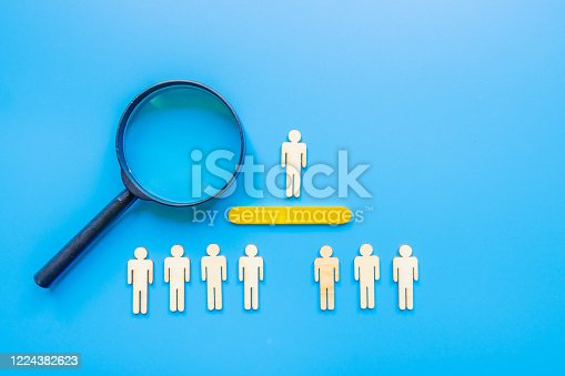 898212112 istock photo Selected wooden figure on blue background. The concept of finding an employee in business. HR manager search employee. Group leader. 1224382623